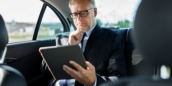 business man using tablet in moving vehicle