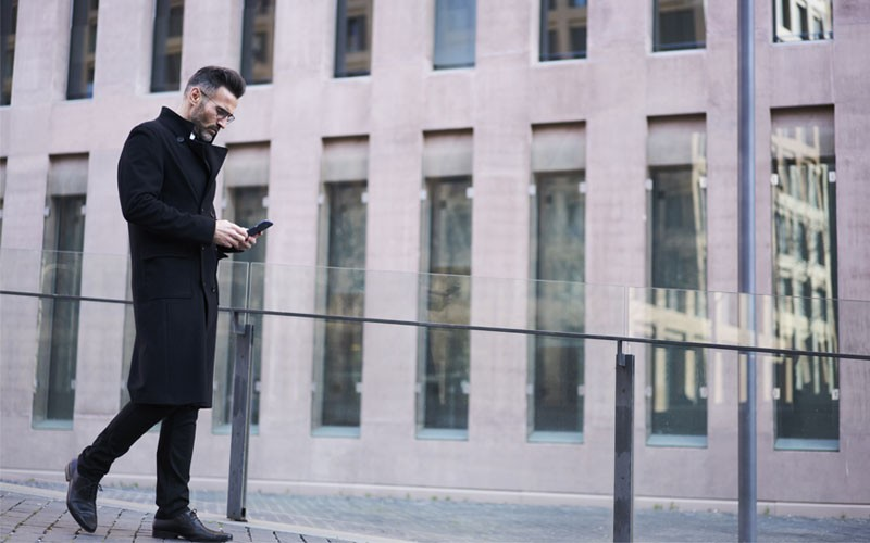 Business man walking outside using cell phone